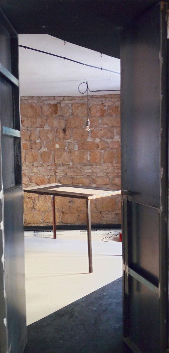 porta in ferro, parete in pietra, tavolo su misura in legno e ferro