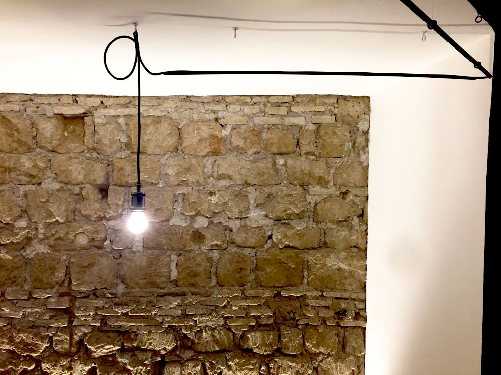 una lampada progettata ad hoc illumina la parete in pietra